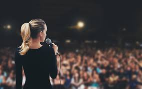 Picture of lady with ponytail speaking in microphone to a large crowd