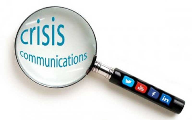 "A hand magnifier placed over the words ""crisis communications"""