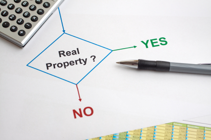 picture of a chart with real property? connecting to no or yes, with a pen and calculator on top.