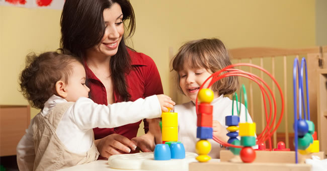 A female adult playing with toddlers