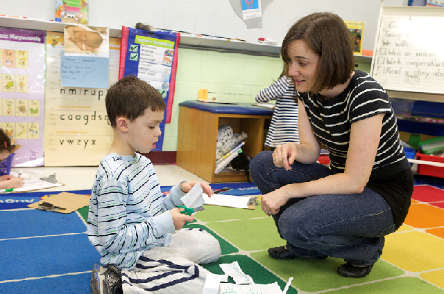 Teacher and a student talking in a classroom