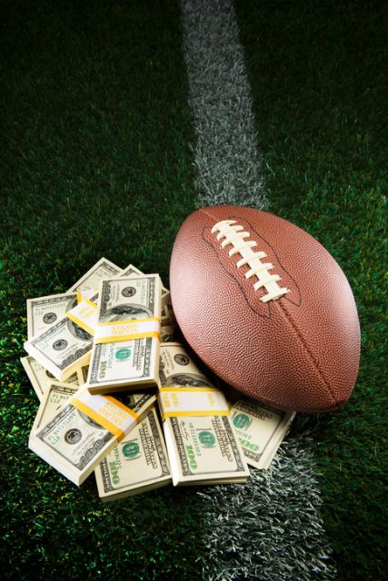 a stack of cash next to a football on a field