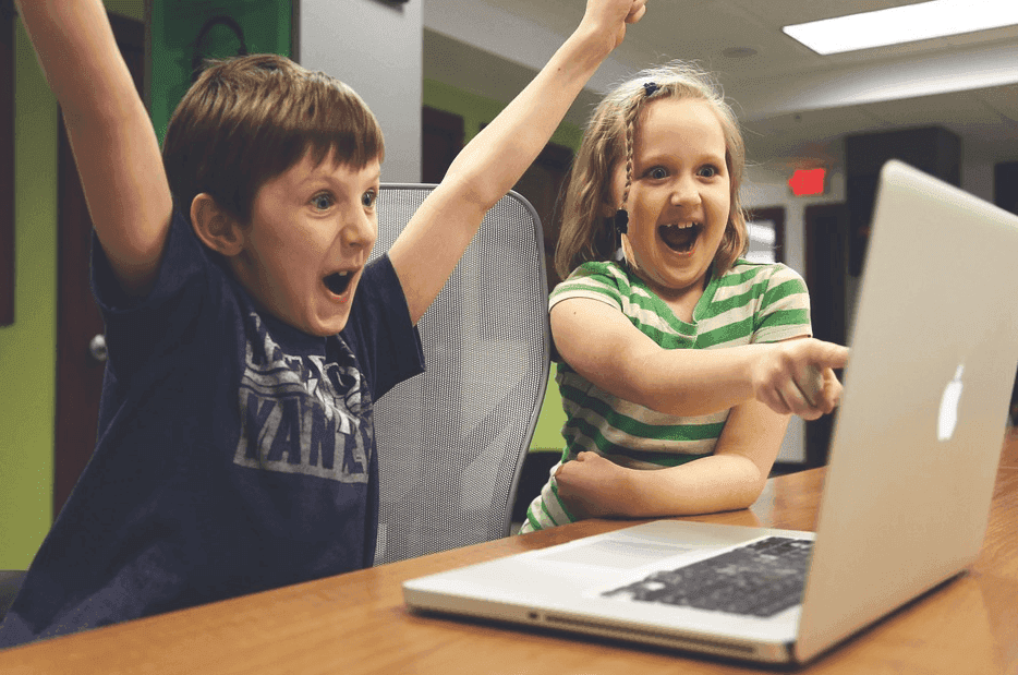 two kids looking happy while using a laptop
