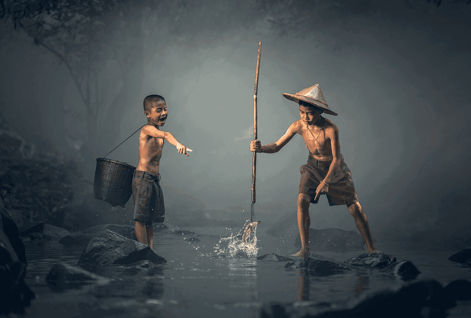 two young boys playing on a river holding a bamboo stick