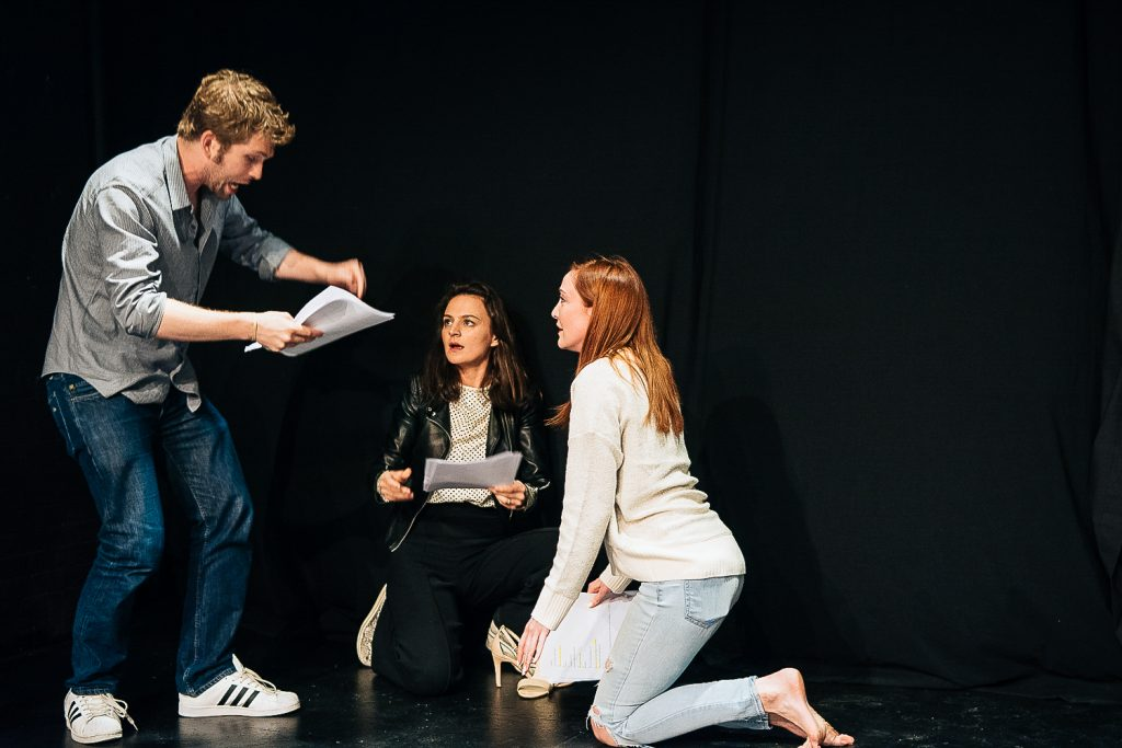 Image of three people reciting a script and acting out the scene.