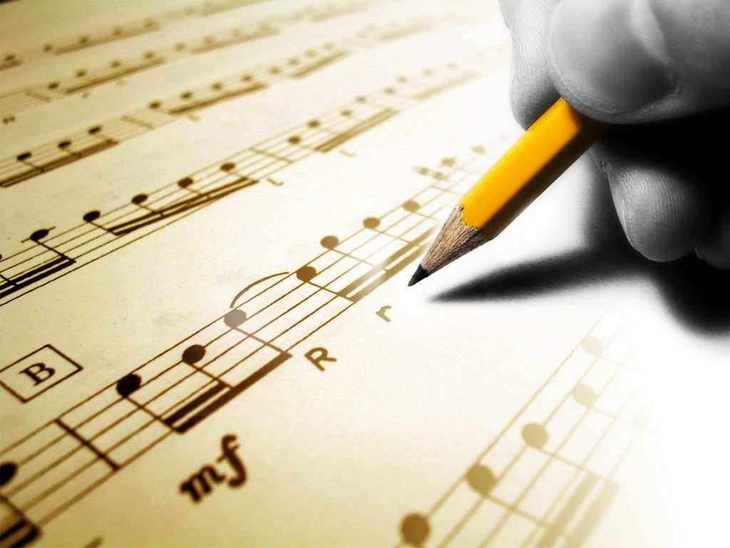 A person holding a pencil writing on music notes