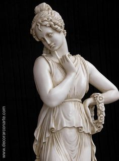 a statue of a Greek female standing with her and on her hip and a finger on her chin.