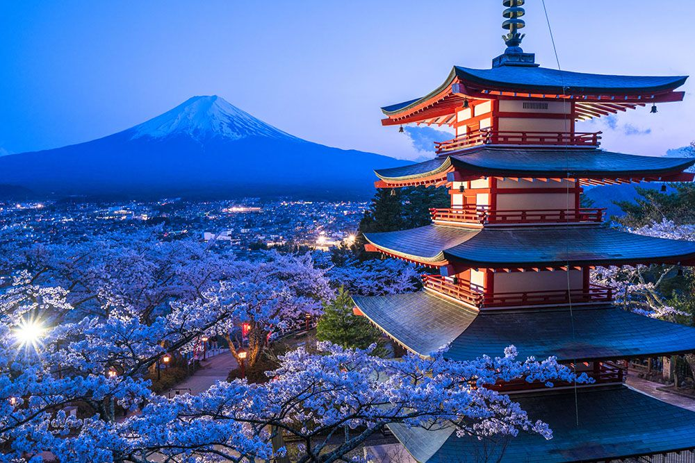 A view of Japan with a temple in the forefront, cherry blossoms, and a mountain in the background.