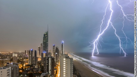 A lightning bolt striking in the ocean next to a big city.