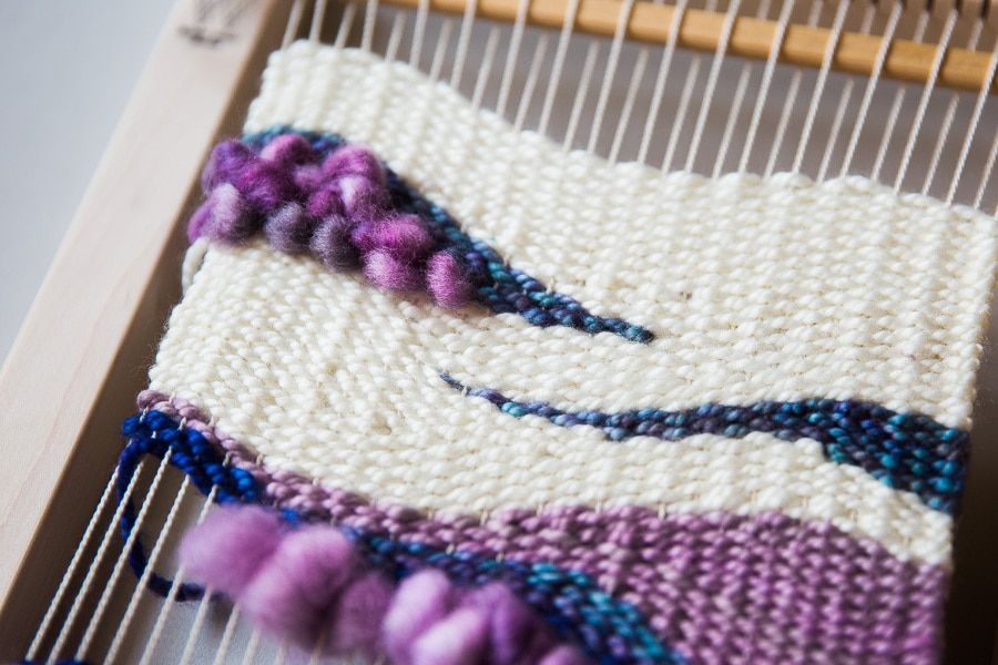 weaving a blanket with purple and blue string