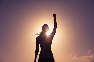 picture of woman looking up with fist in the air as the sun creates a shadow
