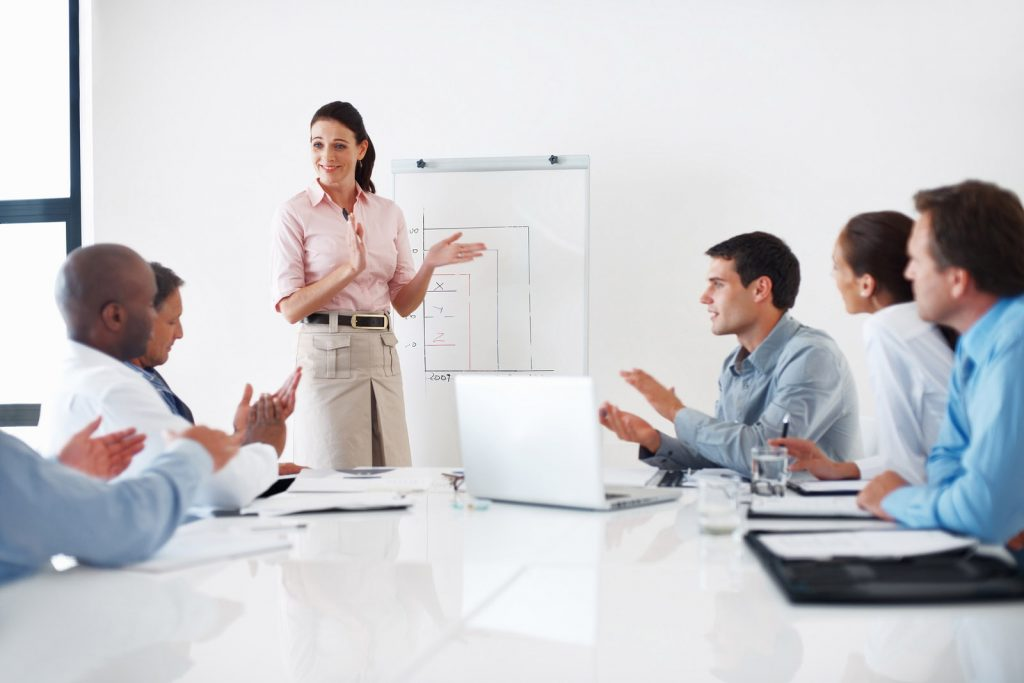 woman presenting to coworkers during a business meeting