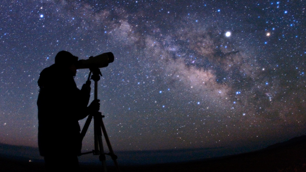 Picture of a person looking through a telescope at a starry sky.