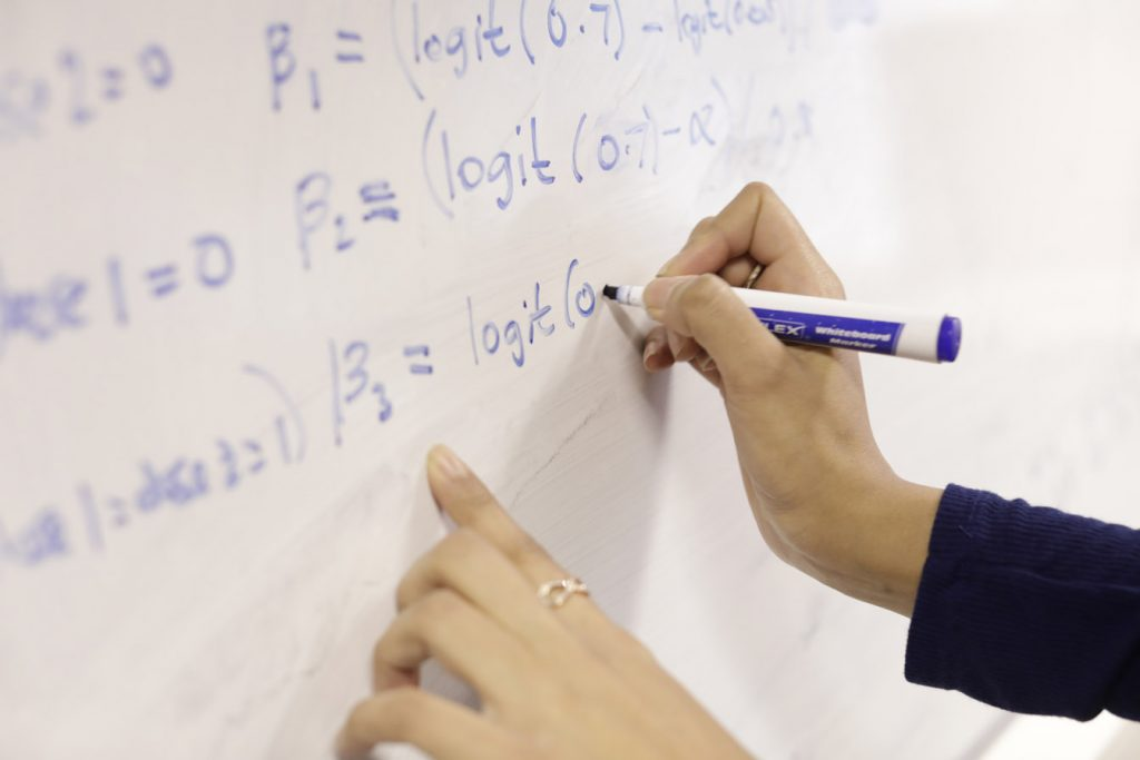 A professor writes some statistical formulas on the board.