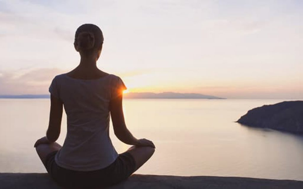 Picture of person meditating in front od sunrise