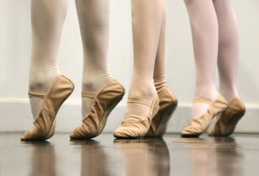 This is an image of four pairs of feet wearing tights and ballet shoes.