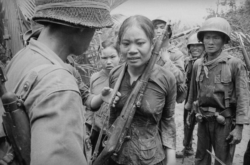 Soldiers from the Vietnam war speaking to a woman