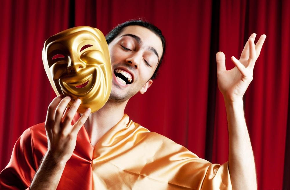 An Actor on stage holding a mask
