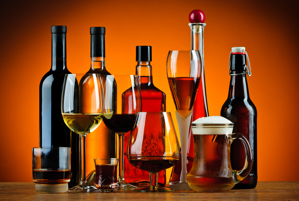 An assortment of wines and beers in bottles and glasses