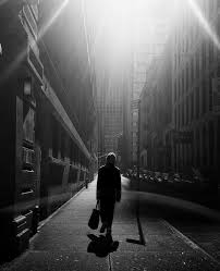 black and white photograph, with man walking through city streets