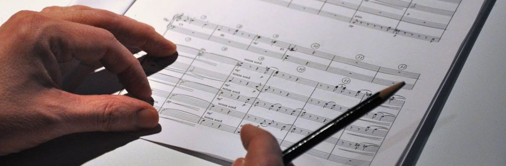 An image of a person's hand over a music book