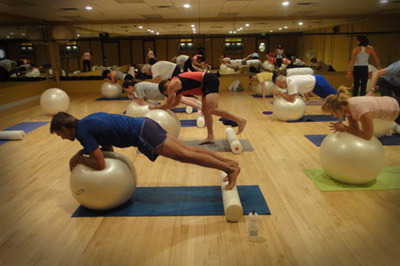 A fitness class that does core work with mats and exercising balls.