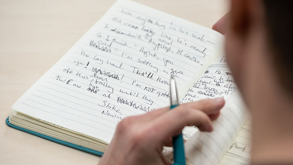 This is an image of a person writing in a notebook.