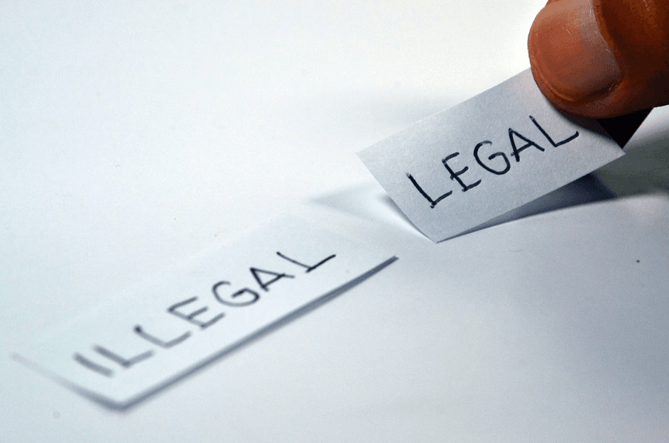 picture of two pieces of paper, one with the word illegal and another with legal