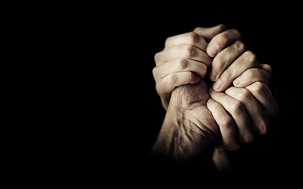 black background, three hands holding  each other to the right