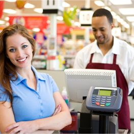 a manager in front of a cashier smiling