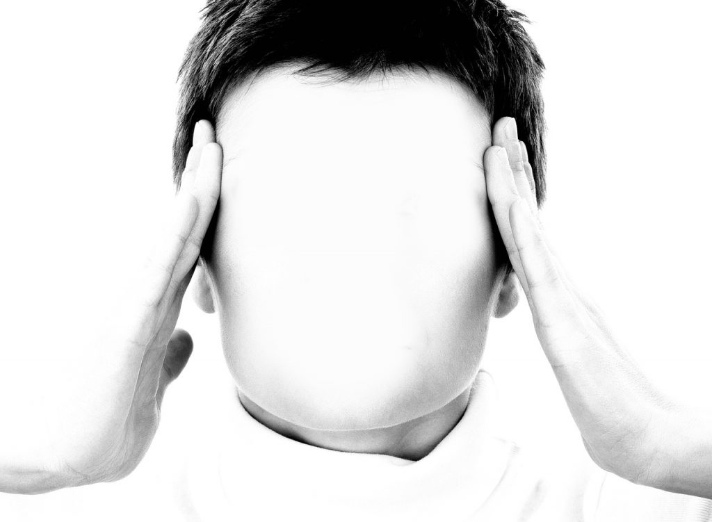 picture of a faceless person holding their forehead