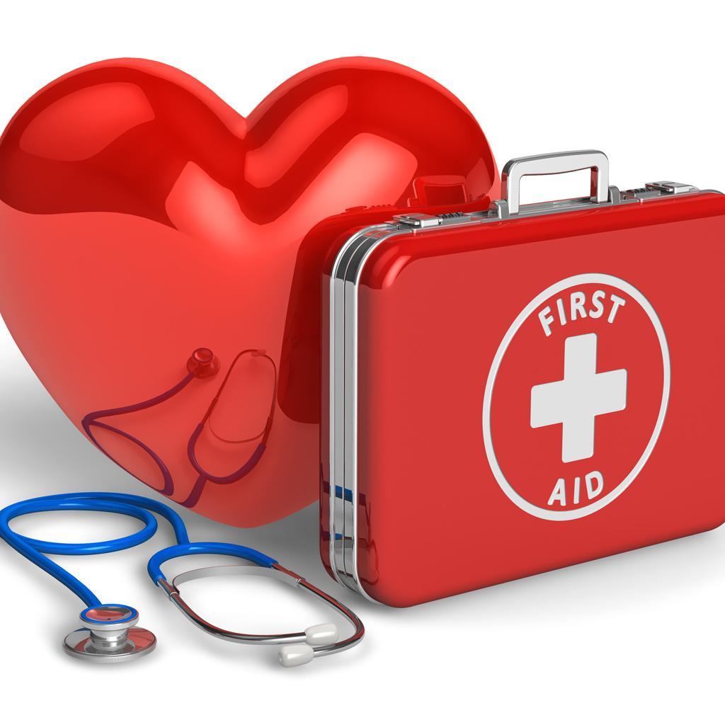 A heart model, a stethoscope, and a red briefcase written FIRST AID