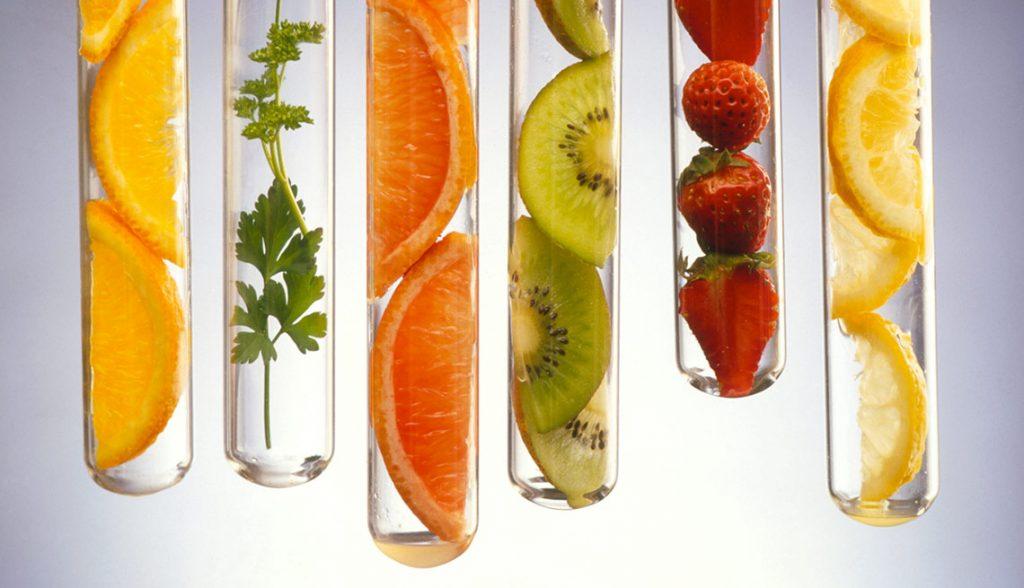 food in test tubes; orange slices, herb, grapefruit slices, kiwi slices, strawberries, orange slices