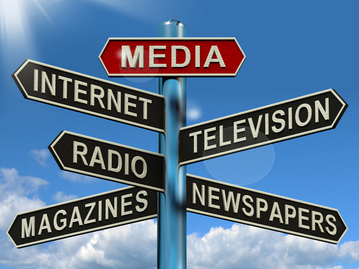 A street sign labeled mass media with categories of media below it.
