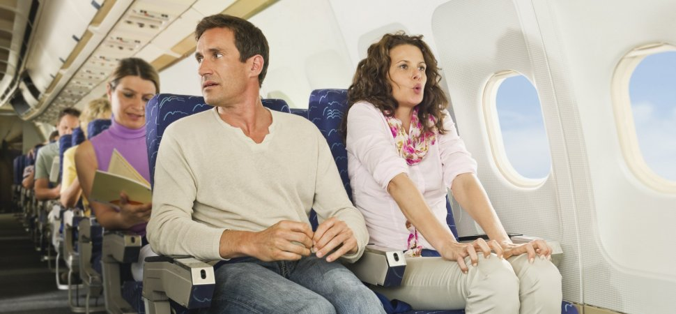 Image of two people sitting in a plane and looking nervous.