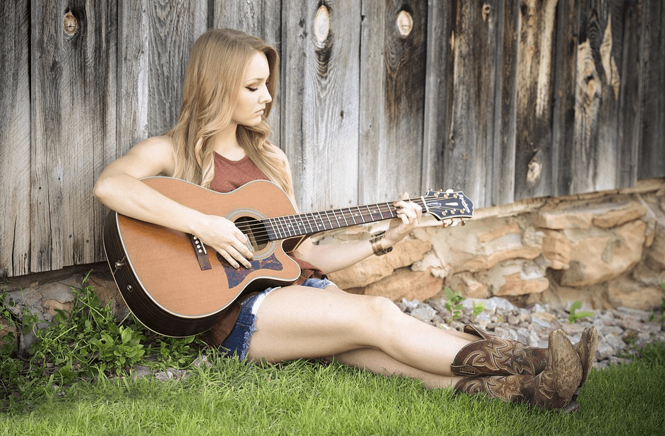 girl sitting on the ground while playing the guitar