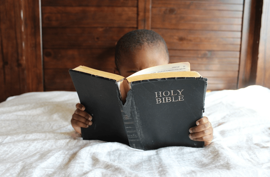 kid reading the holy bible in bed
