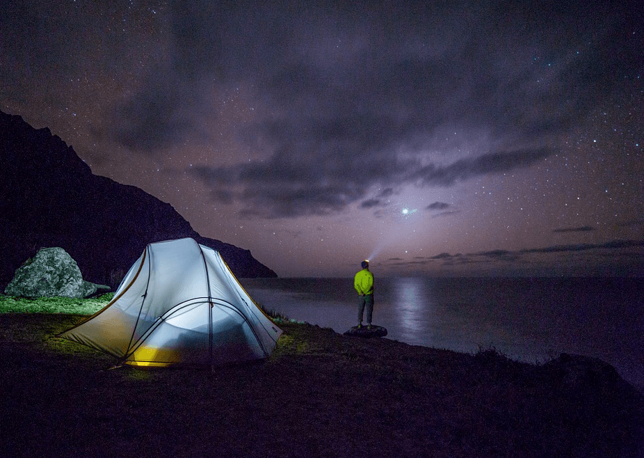 man with a tent looking at the night sky