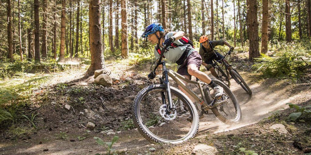 mountain biking in woods, man and woman