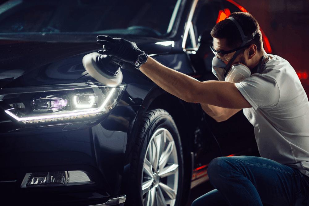 A person detailing a car