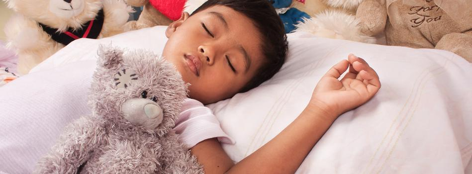 A child sleeping in bed surrounded by plush animals