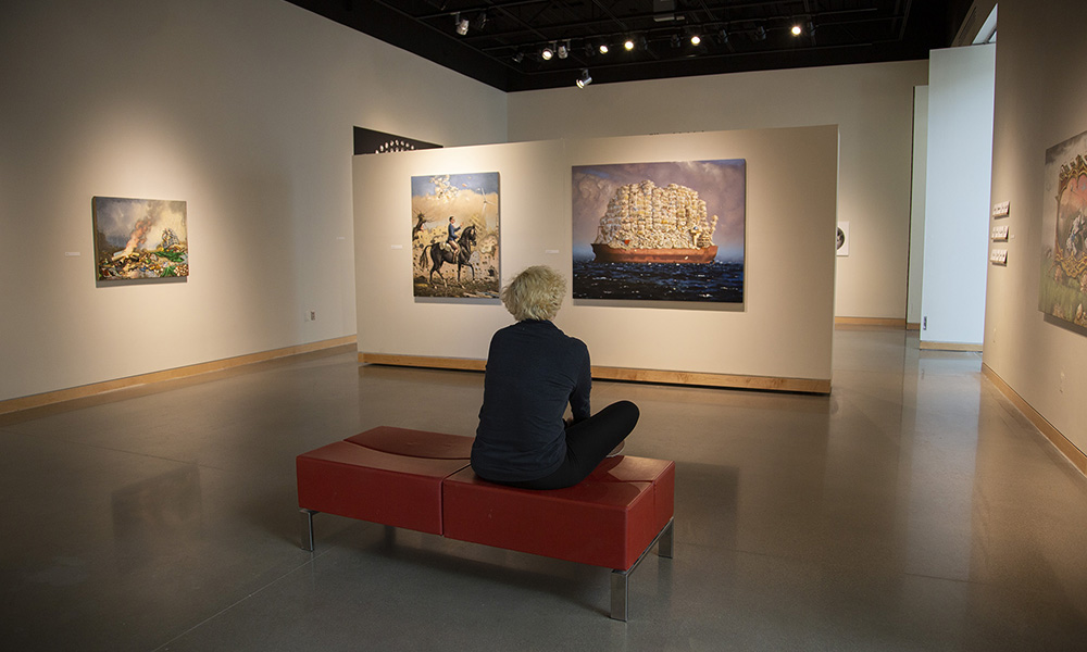 picture of a person in an art gallery sitting on a bench