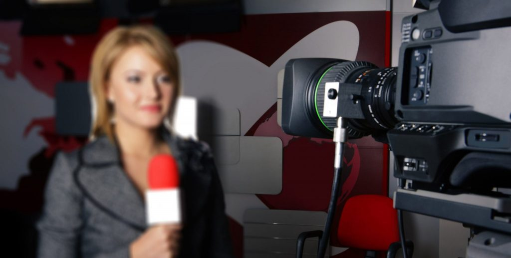A female reporting in front of a news camera