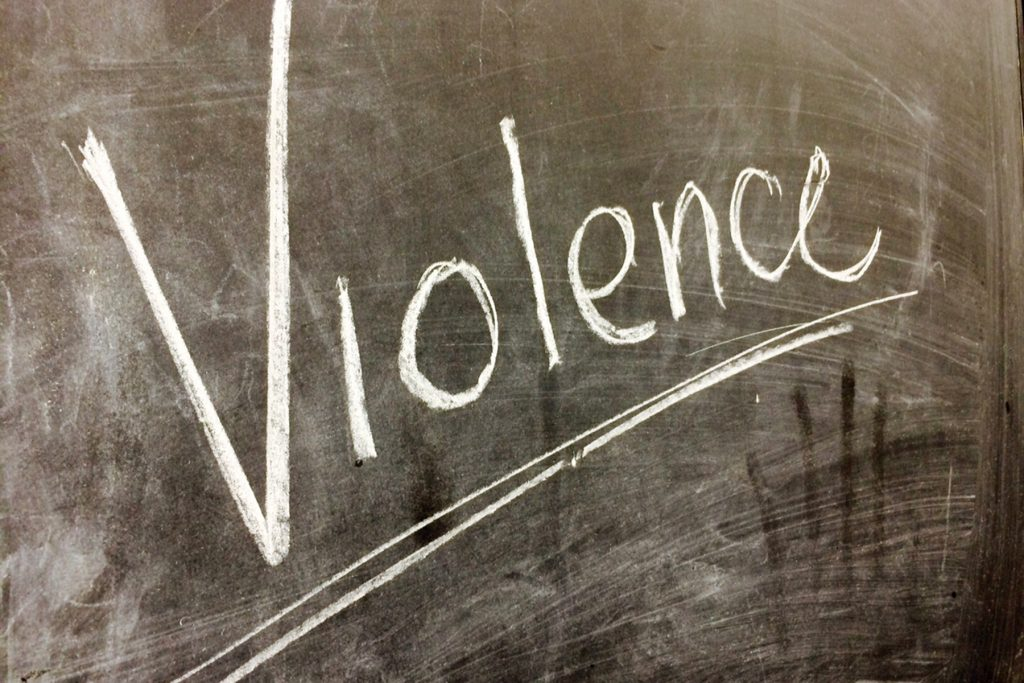 The word Violence written on a chalkboard and underlined.
