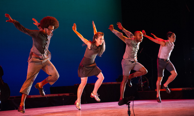 a group of people on stage tap dancing during a theatre performance