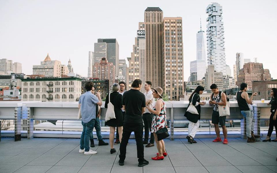 a group of young professionals networking on the rooftop with a background of the cityline