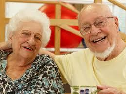 An older lady and a man smiling while sitting down next to each other.