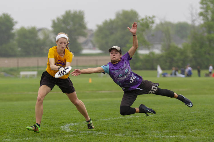 Two players on different teams playing ultimate frisbee and trying to jump grab the frisbee.
