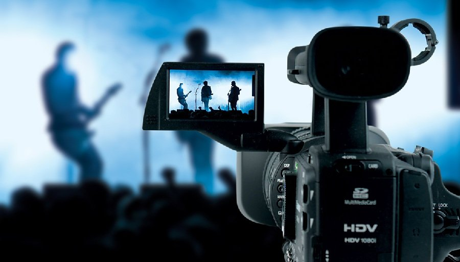 A digital camera filming a scene of a concert happening on stage