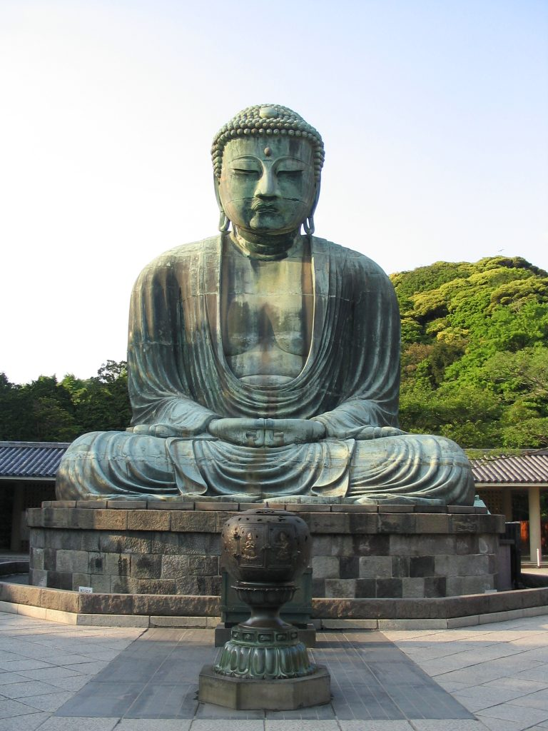 A statue of Buddha sitting surrounded by a pool of water.